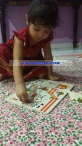 Iman sedang bermain wooden knob puzzle sebagai latihan untuk jarinya memegang objek menggunakan 3 jari
