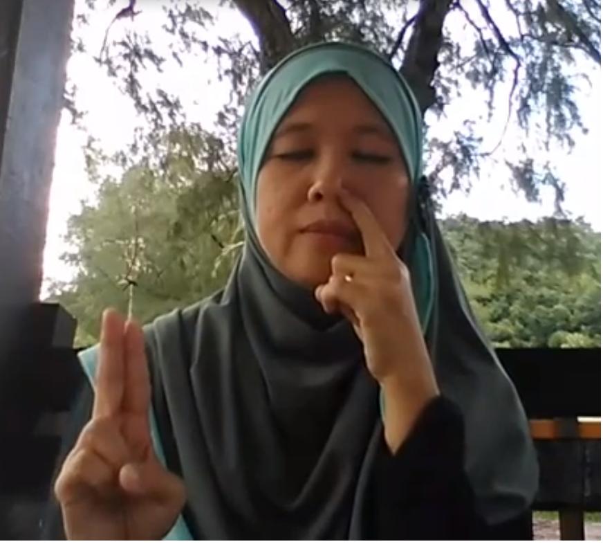 Puan Maznah Ibrahim sedang menunjukkan teknik untuk melakukan relaksasi pernafasan untuk mengatasi masalah sakit kepala