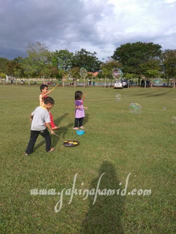 Kanak-kanak main belon buih di padang